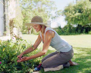 Woman wearing straw hat kneeling down tending to garden, smiling
